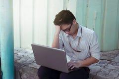 Giovane uomo asiatico frustrato depresso di affari che per mezzo del computer portatile che sembra serio fotografie stock libere da diritti