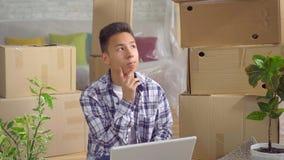 Giovane uomo asiatico premuroso dopo essere mosssi verso un nuovo appartamento che si siede ad un computer portatile sul paviment stock footage