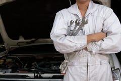 Giovane uomo asiatico professionale del meccanico in chiave uniforme della tenuta contro l'automobile in cappuccio aperto al gara fotografia stock libera da diritti