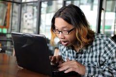 Giovane uomo asiatico rilassato dei pantaloni a vita bassa che lavora contro il computer portatile nel suo ufficio Immagini Stock Libere da Diritti