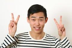 Giovane uomo asiatico sorridente che dà due segni di vittoria e che esamina Fotografie Stock Libere da Diritti