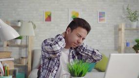 Giovane uomo asiatico in una camicia con dolore al collo che si siede al computer portatile video d archivio