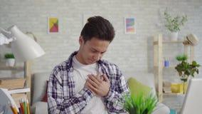 Giovane uomo asiatico in una camicia con un'angustia che si siede al computer portatile stock footage