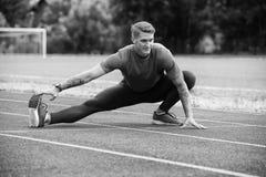 Giovane uomo atletico che allunga prima dell'esercizio corrente Immagine Stock Libera da Diritti