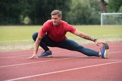 Giovane uomo atletico che allunga prima dell'esercizio corrente Immagine Stock