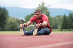 Giovane uomo atletico che allunga prima dell'esercizio corrente Immagini Stock