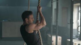 Giovane uomo atletico che dowing tirata-UPS sulla corda che scala nella palestra spaziosa movimento lento 4k archivi video