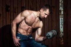 Giovane uomo atletico che fa allenamento con la testa di legno pesante Immagini Stock Libere da Diritti