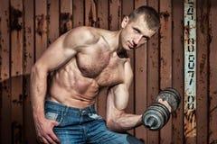 Giovane uomo atletico che fa allenamento con la testa di legno pesante Immagine Stock Libera da Diritti
