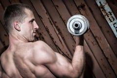 Giovane uomo atletico che fa allenamento con la testa di legno pesante Fotografie Stock Libere da Diritti