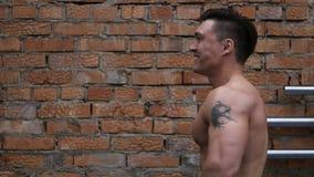 Giovane uomo atletico che posa vicino al muro di mattoni archivi video