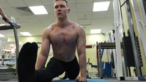 Giovane uomo atletico che si scalda allungamento prima dell'addestramento sul pavimento nella palestra