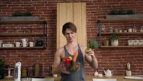 Giovane uomo atletico del vegano che tiene i broccoli e ciotola con la verdura sulla cucina a casa Alimento e sano sani video d archivio