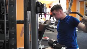 Giovane uomo atletico eseguire gli esercizi del muscolo dorsale sulla macchina di esercizio della barra di pulldown in palestra stock footage