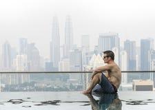 Giovane uomo attraente alla piscina in tetto al grattacielo Fotografie Stock
