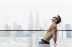 Giovane uomo attraente alla piscina in tetto al grattacielo Fotografia Stock Libera da Diritti