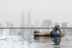 Giovane uomo attraente alla piscina in tetto al grattacielo Fotografia Stock