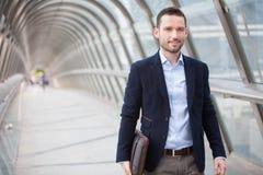 Giovane uomo attraente che cammina in un corridoio dell'aeroporto immagini stock