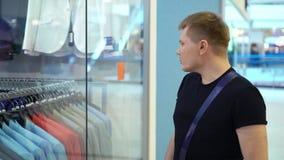 Giovane uomo attraente che esamina la finestra del negozio con i vestiti degli uomini nel centro commerciale video d archivio