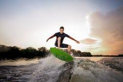 Giovane uomo attraente che fa un salto sul wakeboard verde immagini stock libere da diritti