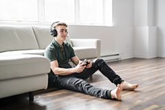 Giovane uomo attraente che gioca i video giochi nel salone fotografia stock