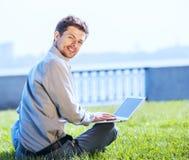 Giovane uomo attraente che lavora al computer portatile all'aperto Immagine Stock