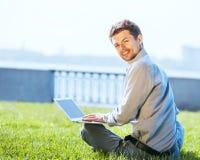 Giovane uomo attraente che lavora al computer portatile all'aperto Immagini Stock Libere da Diritti