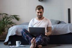 Giovane uomo attraente che si siede sul pavimento nella nel suoi camera da letto e lavoro fotografia stock