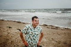Giovane uomo attraente che tira alla sua camicia contro fotografie stock