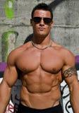 Giovane uomo attraente del muscolo sulla parete dei graffiti Fotografie Stock