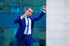 Giovane uomo attraente di affari in vestito che celebra successo, demone fotografia stock libera da diritti