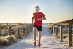 Giovane uomo attraente e felice del corridore di sport con la misura ed il forte addestramento sano del corpo fuori dalla pista d immagine stock libera da diritti