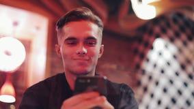 Giovane uomo attraente facendo uso dello smartphone alla sera Lui che si siede in una barra o in un ristorante vicino al contrass archivi video