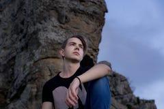 Giovane uomo attraente individuato con sulla cima delle montagne immagine stock libera da diritti