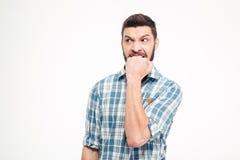 Giovane uomo barbuto aggressivo irritato arrabbiato che morde il suo pugno immagine stock libera da diritti