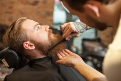 Giovane uomo barbuto allegro al salone di capelli Immagini Stock