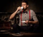 Giovane uomo barbuto antiquato bello con la tazza di caffè che si siede sul sofà di cuoio comodo su fondo scuro Immagini Stock