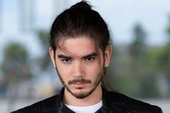 Giovane uomo barbuto bello che posa esterno immagine stock libera da diritti