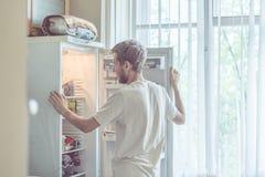 Giovane uomo barbuto bello che sta vicino alla cucina opended del frigorifero a casa immagine stock libera da diritti