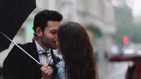 Giovane uomo barbuto bello in un costume elegante ed in una donna attraente minuscola nell'abbigliamento casual con il mazzo del  video d archivio