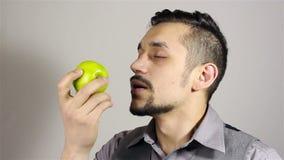 Giovane uomo barbuto che fiuta una mela archivi video