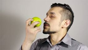 Giovane uomo barbuto che fiuta una mela stock footage