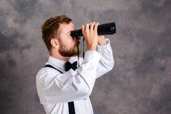 Giovane uomo barbuto che guarda con il binocolo Fotografia Stock Libera da Diritti