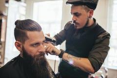 Giovane uomo barbuto che ottiene taglio di capelli in salone fotografie stock libere da diritti