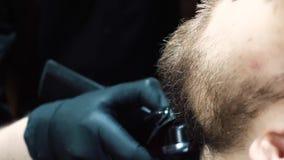 Giovane uomo barbuto che si siede nel parrucchiere video d archivio