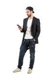 Giovane uomo barbuto con il cappello a rovescio facendo uso del dispositivo del telefono cellulare Immagini Stock