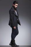 Giovane uomo barbuto di modo in un distogliere lo sguardo lungo del cappotto fotografie stock