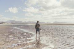Giovane uomo barbuto muscolare che sta sulla riva di mare all'alba Ritratto laterale di giovane funzionamento barbuto sano dell'u Fotografia Stock