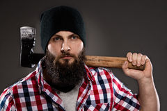 Giovane uomo barbuto sicuro del boscaiolo che porta un'ascia Fotografia Stock