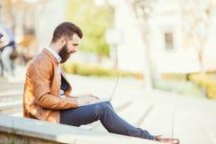 Giovane uomo bello barbuto che si siede sulle scale facendo uso del computer portatile in città Fotografie Stock